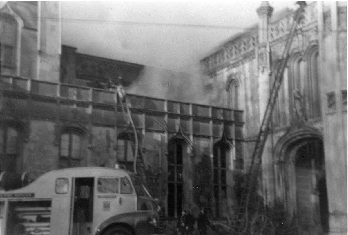 A black and white image of Highcliffe Castle alight during one fires with vintage fire engine and firefighters