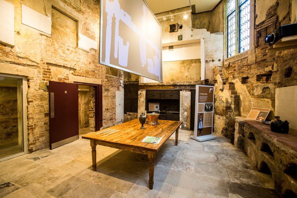 Newly restored kitchen with large wooden table and interactive displays.