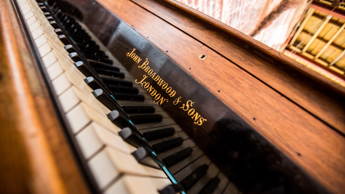 Close up of a piano with gold lettering of maker on it.
