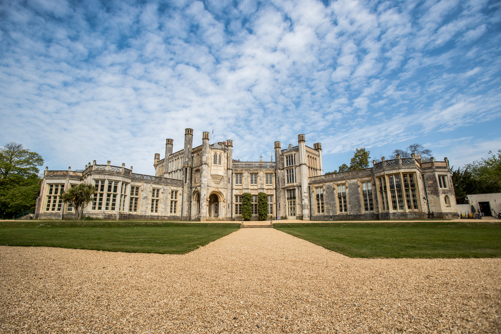 Beautiful blue skies with mottled cloud above Highcliffe Castle with lush green lawns and long gravel paths