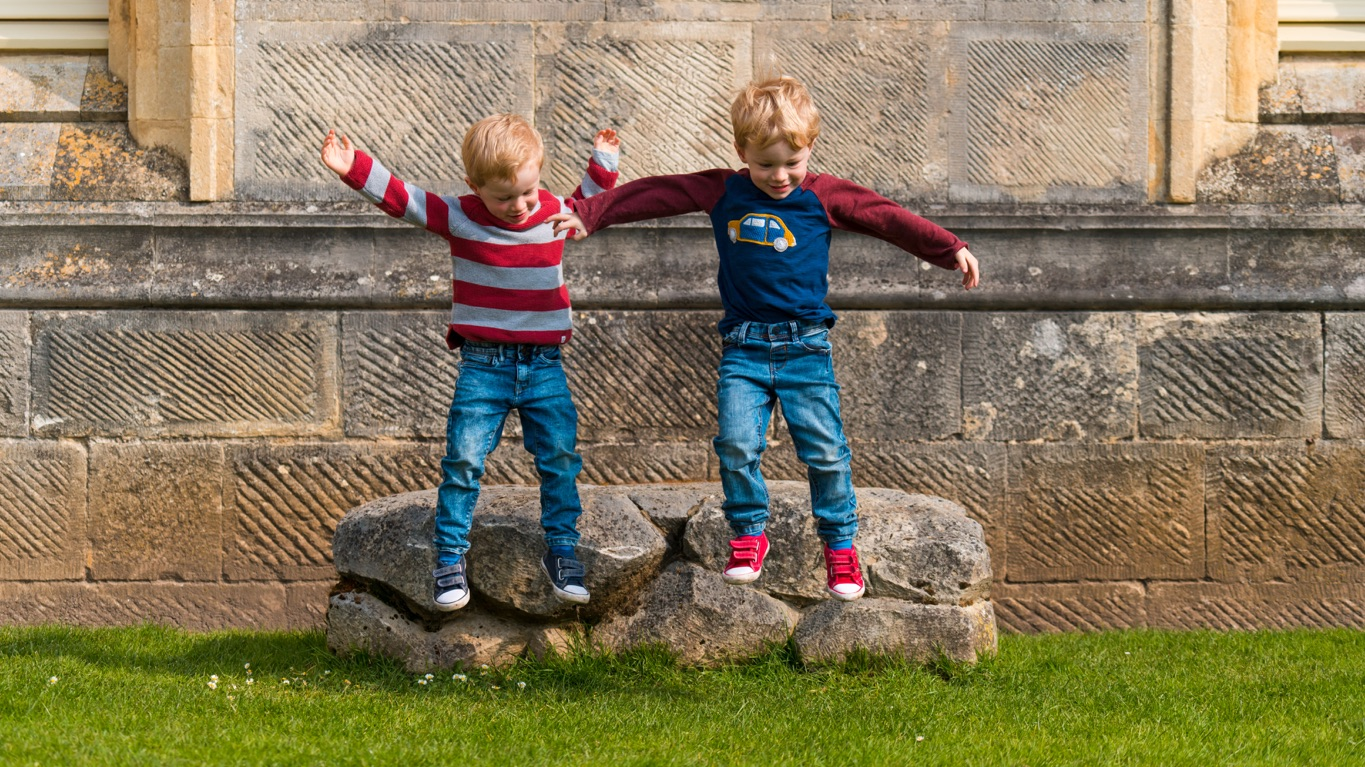 Two young boys in front of the Castle wall, jumping together of off of a large stone on to the grass.