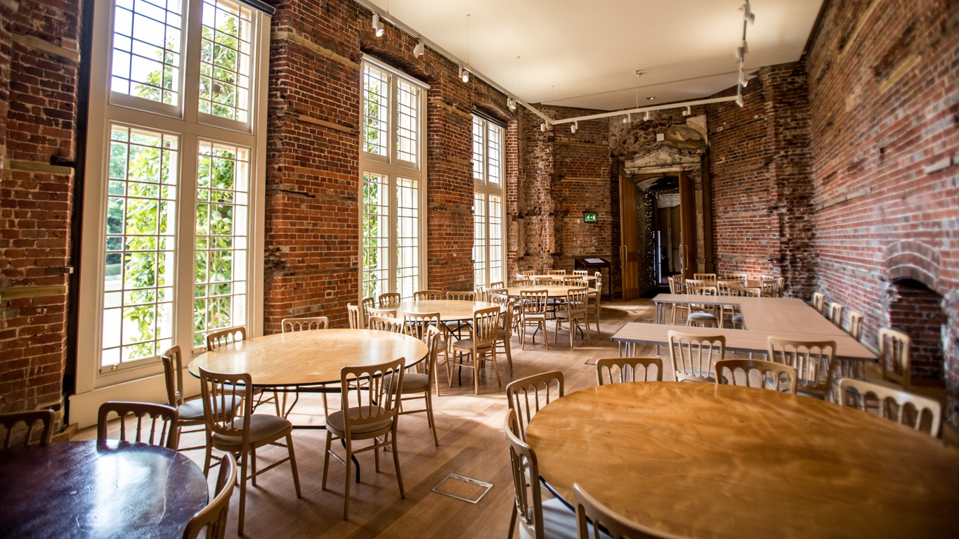 Round wooden tables with chairs for wedding set up in dining room with unrestored brick walls.