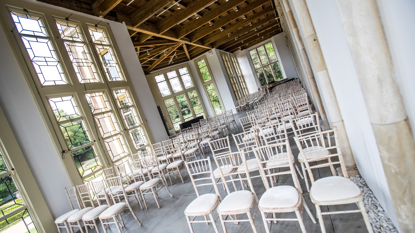 Castle Wintergarden with rows of white chairs, large leaded glass floor to ceiling windows and open timber ceiling.