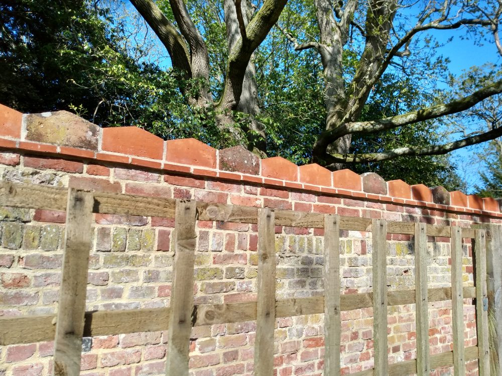 Brick wall with ornate sloping coping stones and trees and blue sky in the background
