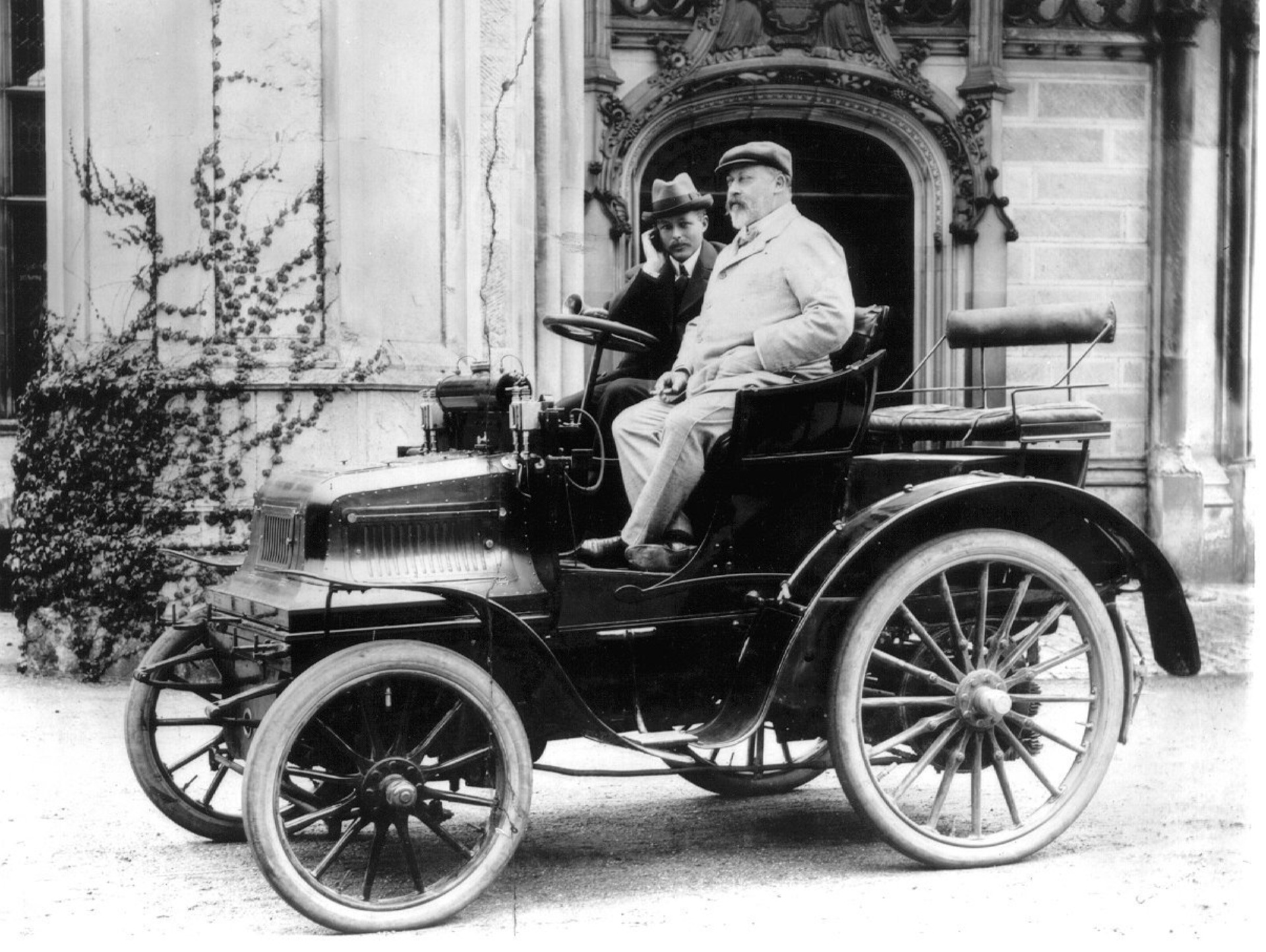 Black and white image of King Edward VII visiting Highcliffe Castle sat in a vintage car with Lord Montagu