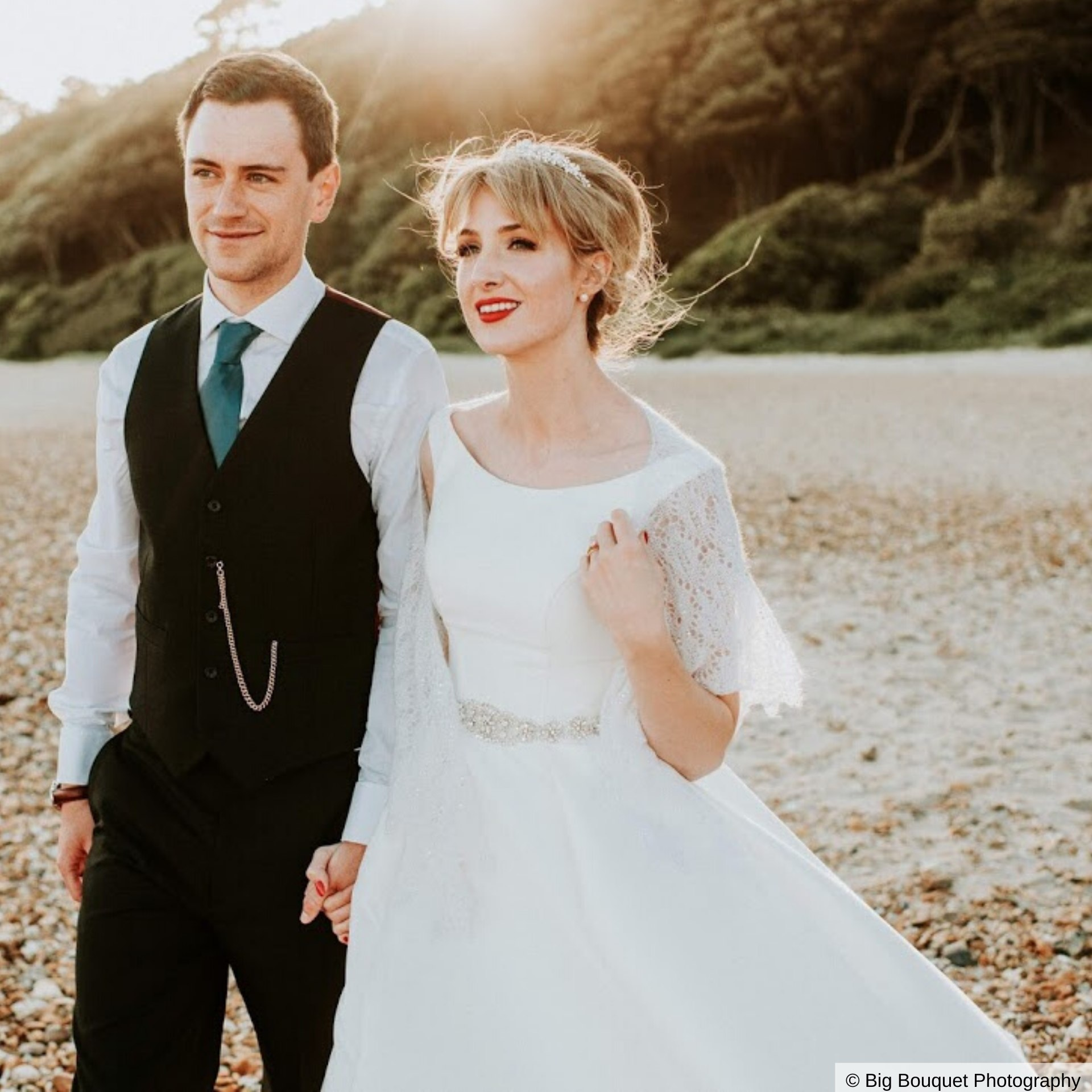 Wedding couple holding hands and walking across Highcliffe Beach at Highcliffe Castle.