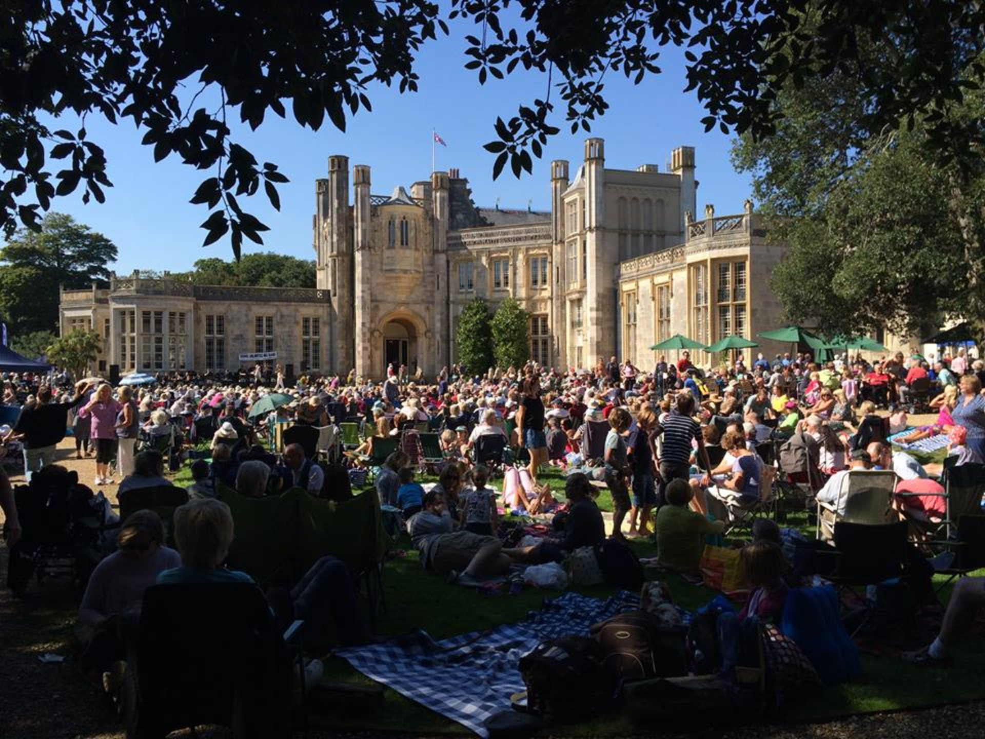 Large gathering of the public watching a live outdoor event at Highcliffe Castle on the grassy lawn