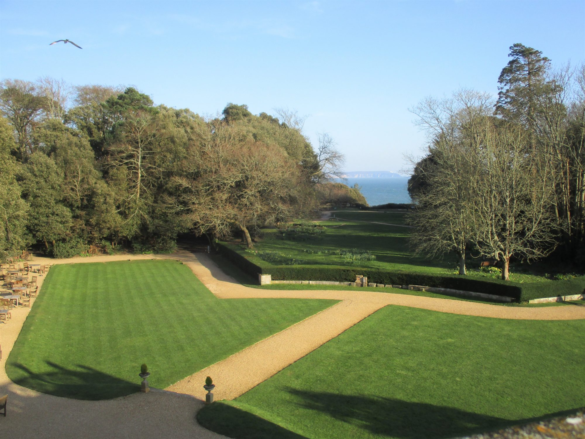 Lawns surrounded by gravel paths and view of the sea between tall trees