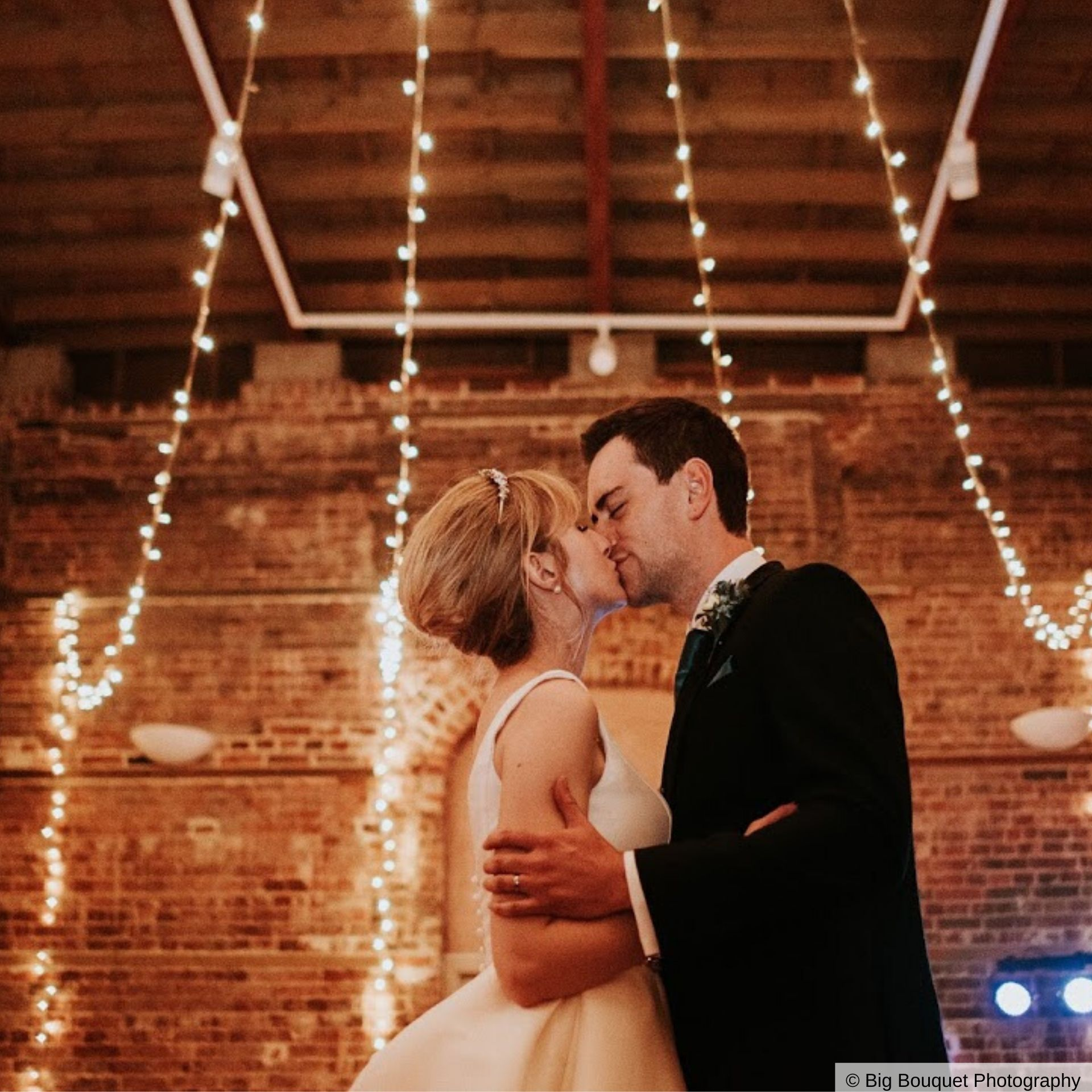Wedding couple kissing in the Drawing Room of Highcliffe Castle with twinkling fairy lights surrounding them.