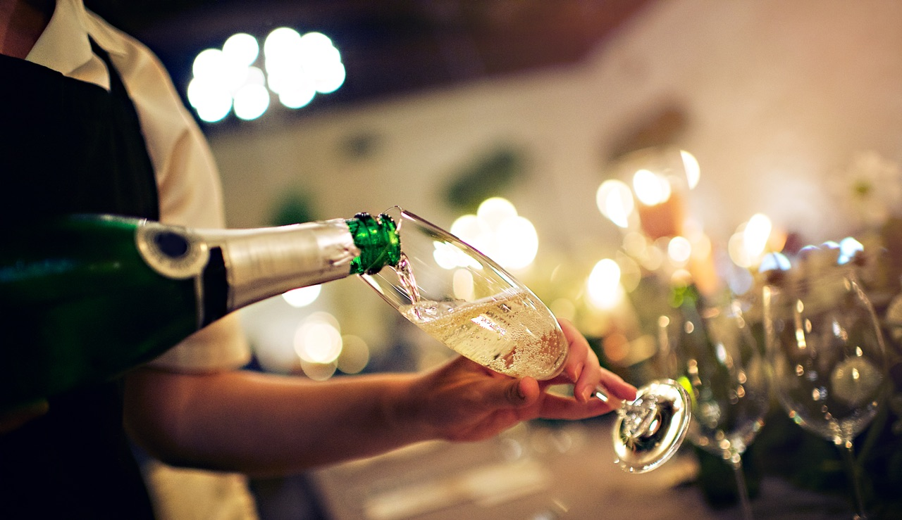 Wedding guest holdinga champagne glass being filled.