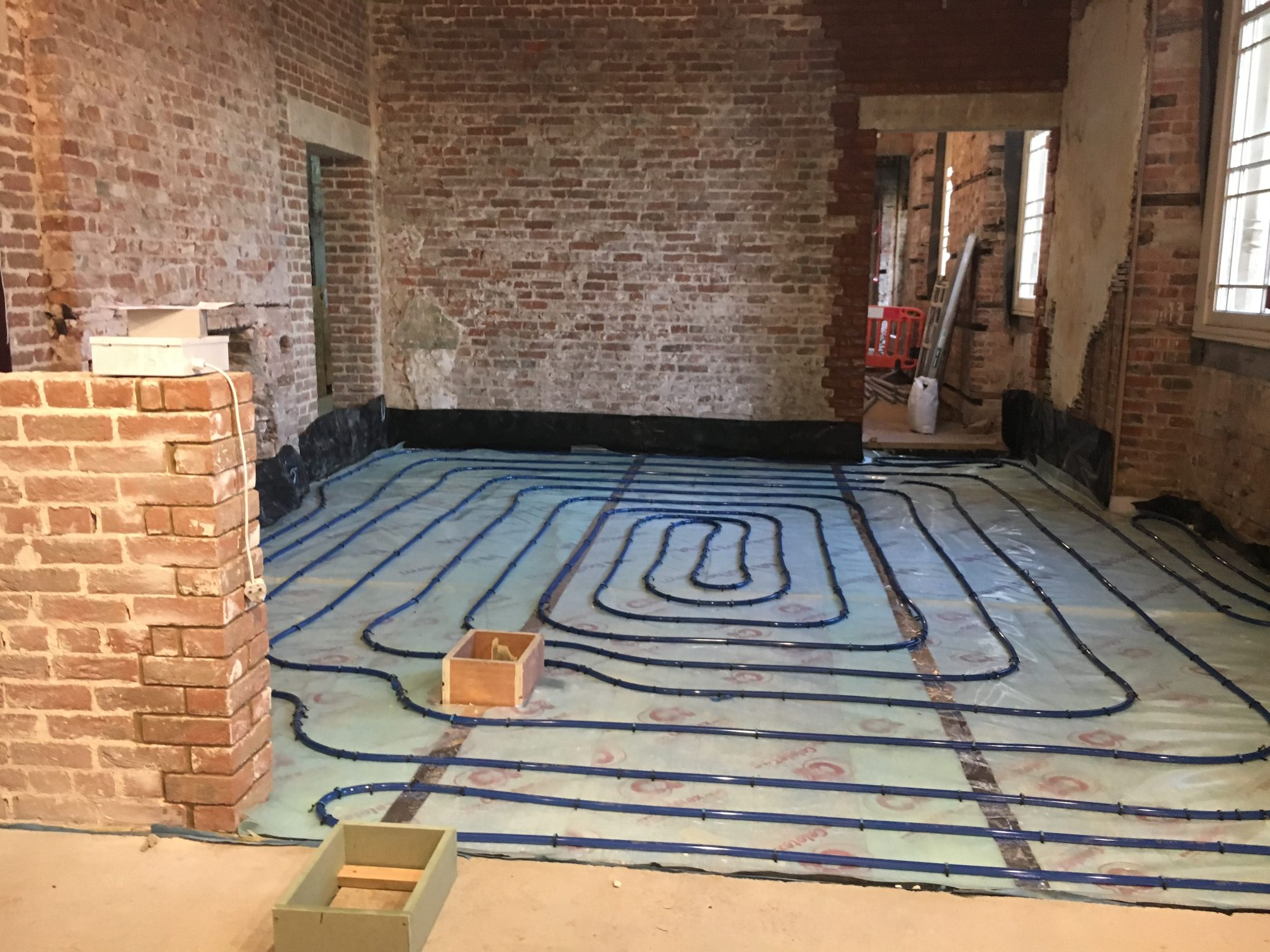 Room with exposed brick walls and cables laid on floor for underfloor heating.