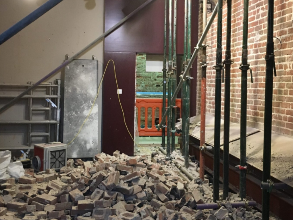 Room with pile of bricks from knocked down wall and steel props holding up ceiling.