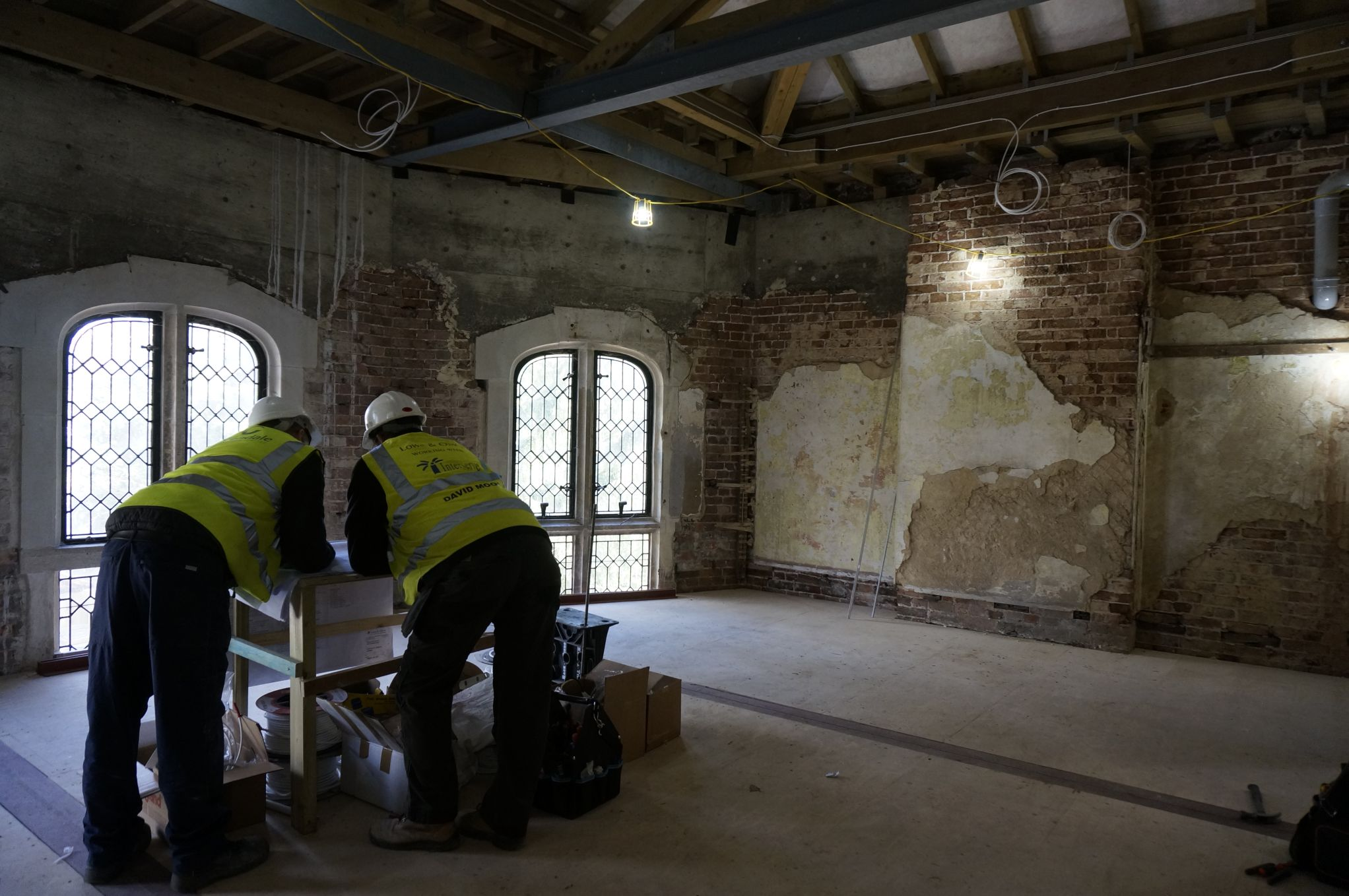 Two men in high vis jackets and hard hats looking over a plan standing in room with exposed brickwork and arched windows.