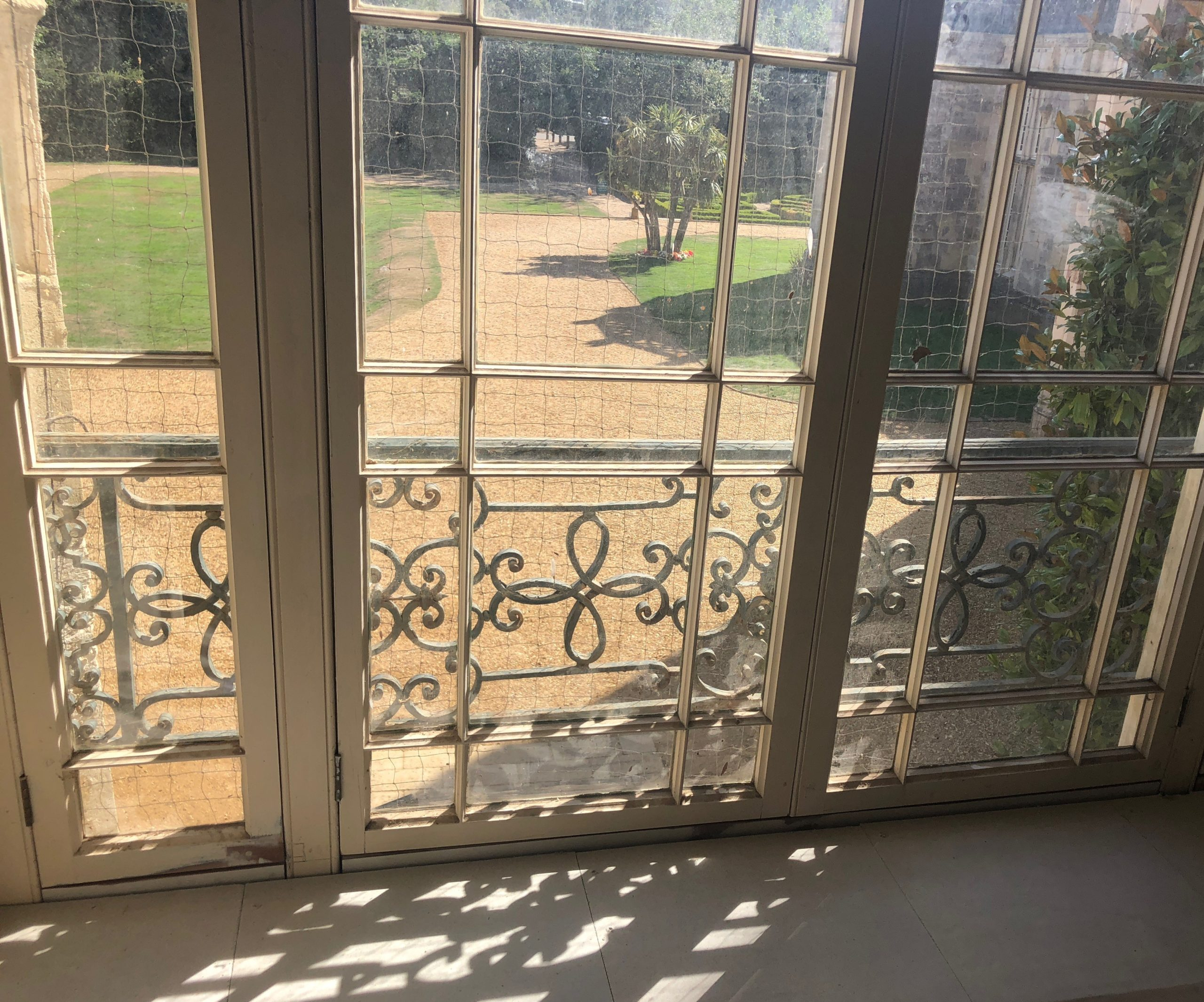Window with ornate metal screen overlooking gravel and lawns