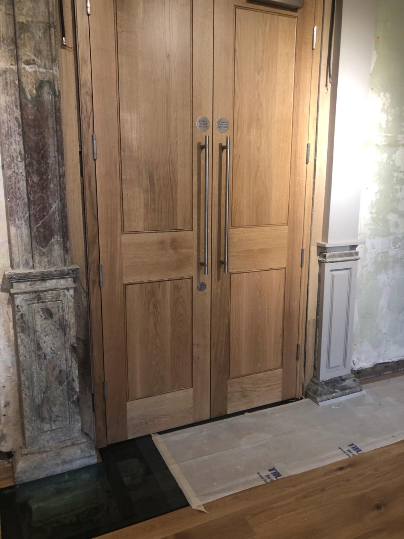 Pair of heavy oak internal doors surrounded by old plasterwork