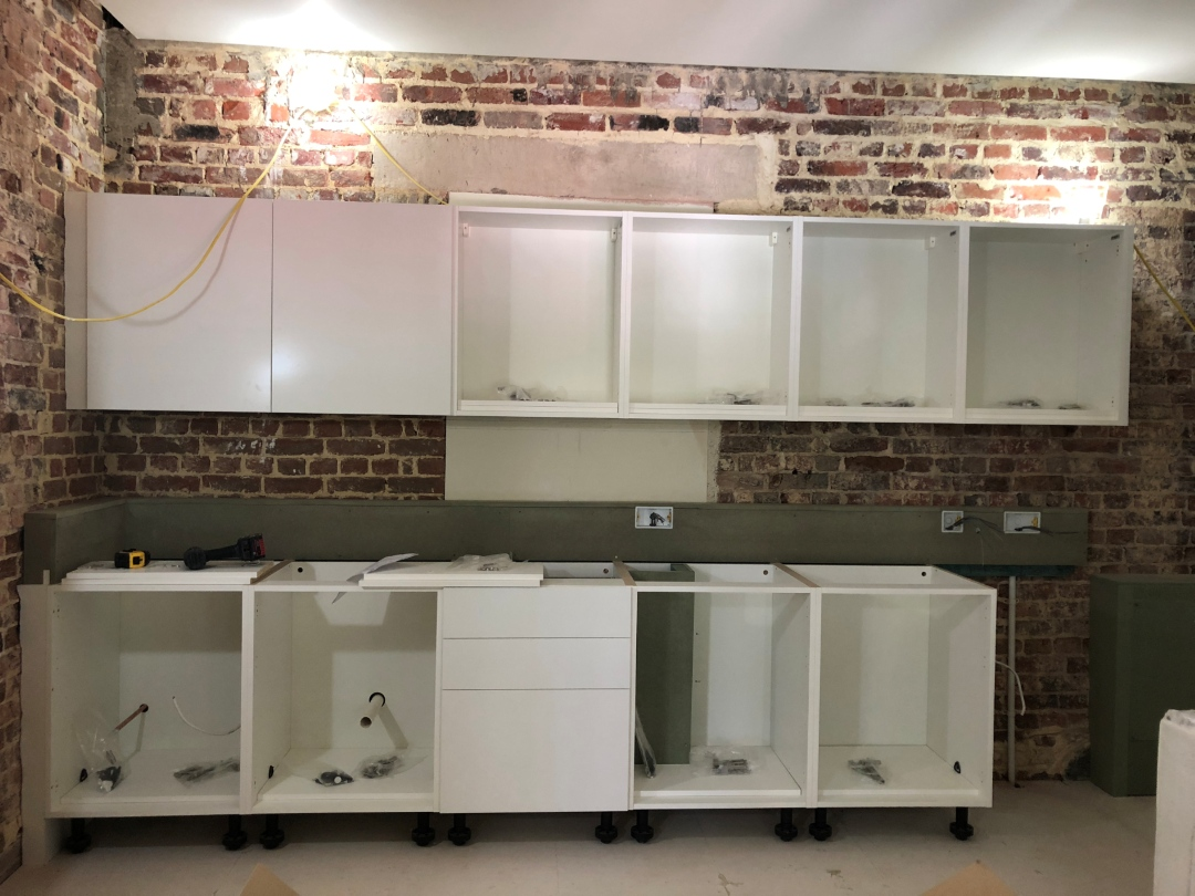 Newly installed white kitchen units against exposed brickwork wall.