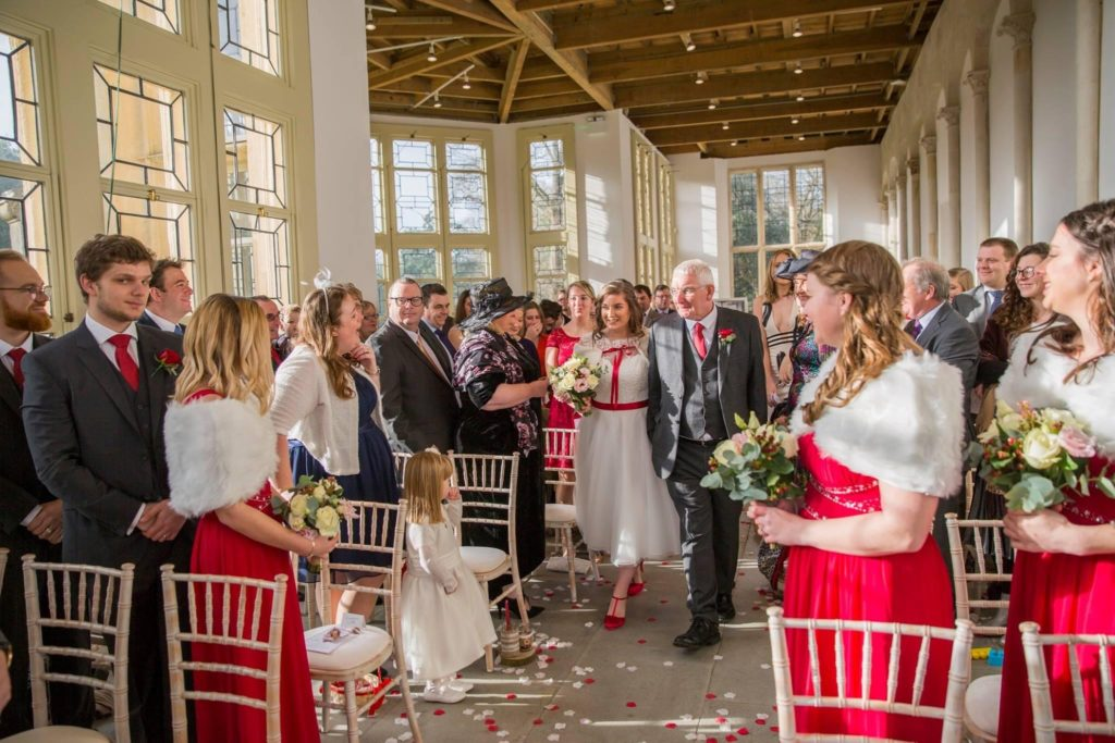Bride walking down the aisle with father as guests watch from their seats