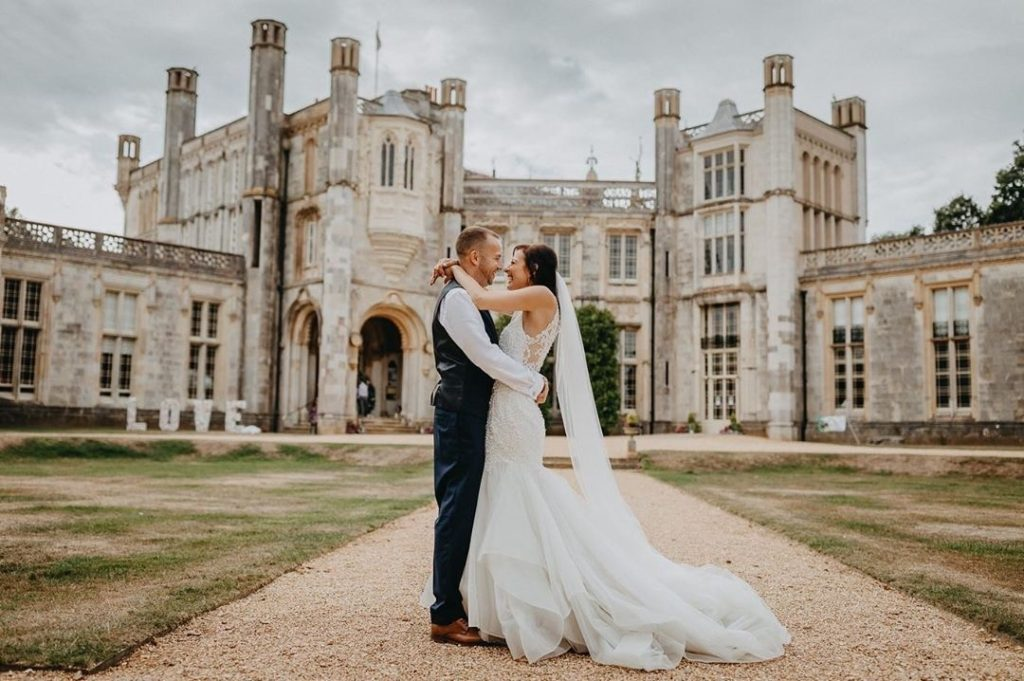 Wedding couple happy and in each others' arms outside Highcliffe Castle