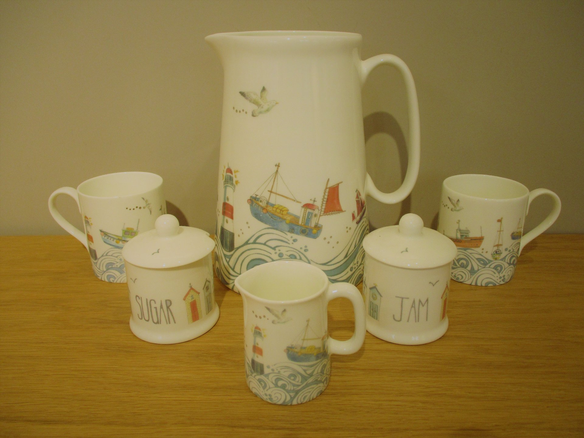 Selection of beach themed ceramics which include beautiful beach hut and sea wave designs