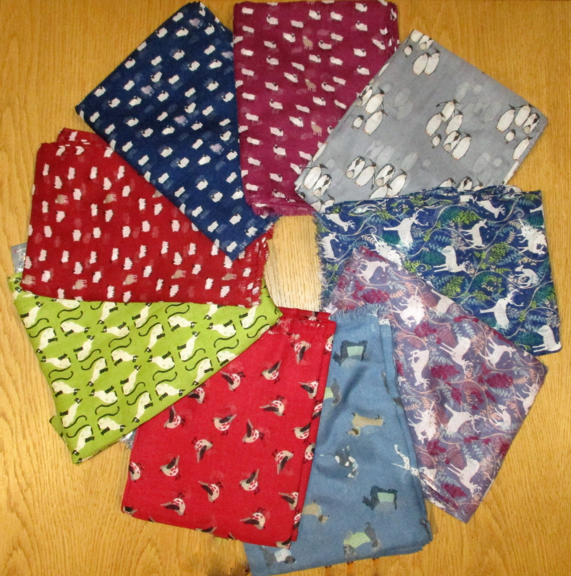 A selection of luxury scarfs in a variety of bright colours and designs including sheep, cats and dogs.